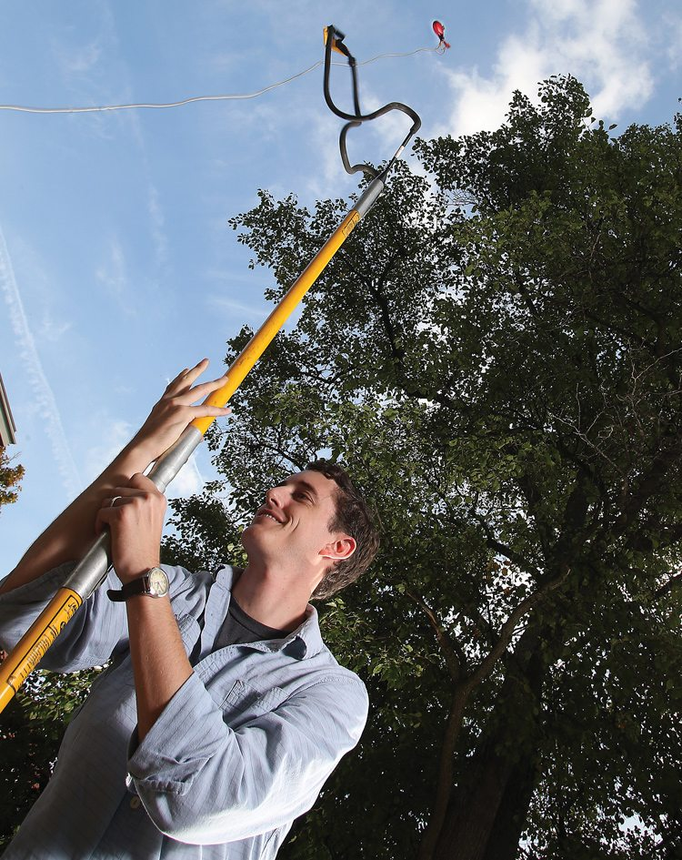 Biology doctoral student Nicholas Smith, shown collecting leaf samples via slingshot, found that including plants' acclimation to temperature improves climate change models. Photo: Tom Campbell, Purdue Agricultural Communication.